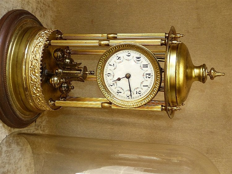A Gilt Metal Anniversary Clock having glass dome, reeded column s