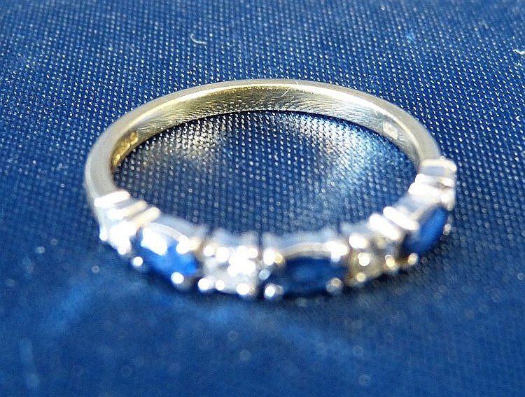 An 18ct Gold Ladies Ring set with 3 sapphires interspersed by 4 s