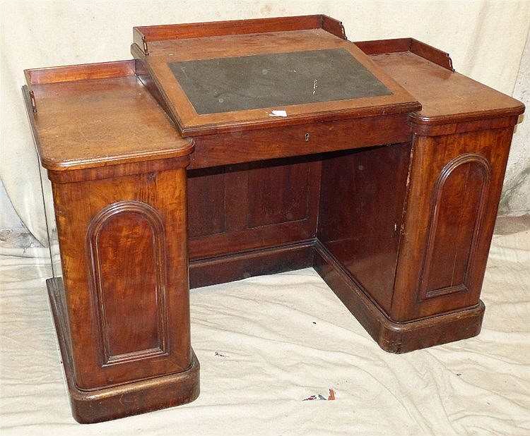 A Victorian Kneehole Desk having sloping hinged top enclosing pig