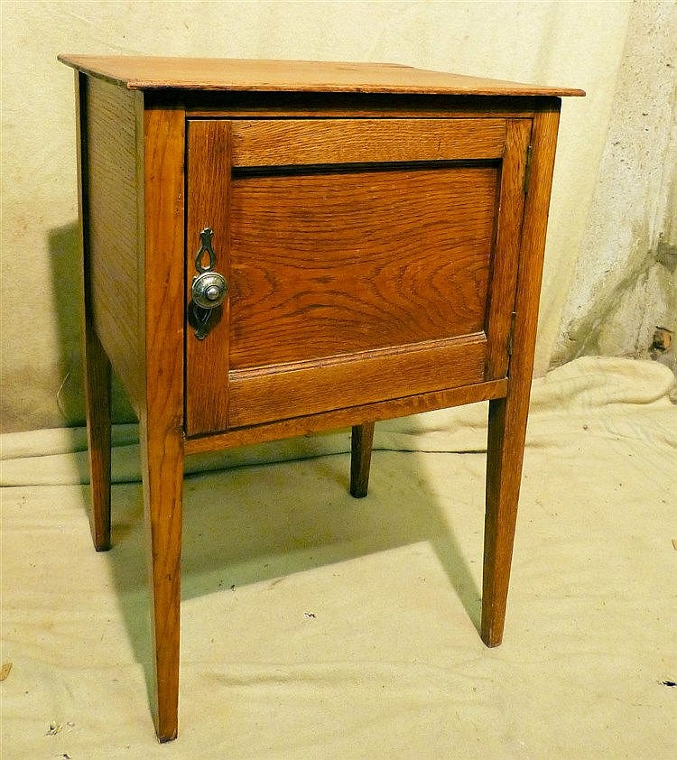 An Oak Bedside Cupboard having single panelled door, on square ta