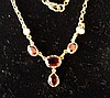 A 9ct Gold Drop Necklace mounted with 4 Garnets and 2 half Pearls