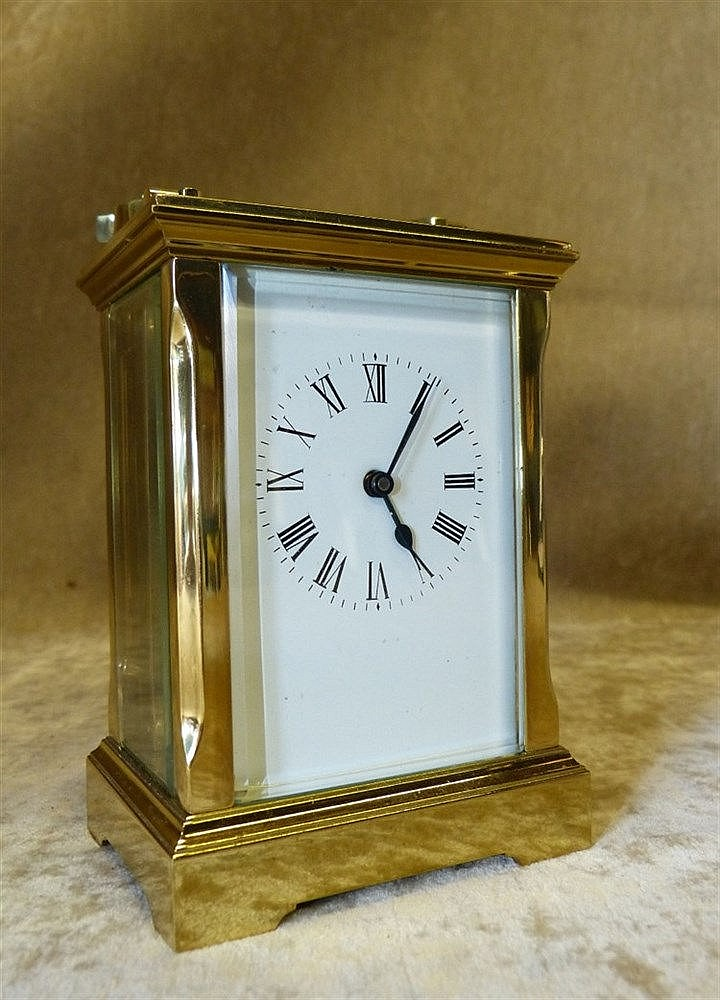 A Brass Carriage Clock having swing overhead handle, white enamel