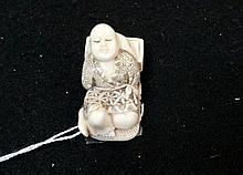 Japanese carved ivory netsuke of man lying in bed, signed on base