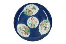 A powder blue large dish with four reserves with Famille Verte floral decoration. With scalloped rim, standing on an elevated ring. Unmarked. China, 19th century. Diam. 35 cm.