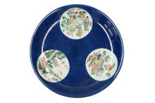 A powder blue large dish with three reserves decorated with figures, antiquities and a river landscape. Unmarked. China, 19th century. H. 5 cm. Diam. 36 cm.