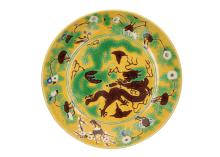 A Sancai porcleain deep dragon dish with a carved and painted decor of five-clawed dragons and burning pearl. The wall inside with a floral decor, the outer side with dragons. Marked Wanli. China, 19th century. H. 6 cm. Diam. 28 cm.