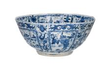 A rare blue and white 'kraak' porcelain bowl with Transitional decor in reserves of figures in a landscape with houses and flowers. The centre with a lady spinning in a window. Unmarked. China, Wanli, ca. 1635-1650. Diam. 35,5 cm. H. 16 cm. For similar example: see 'Kraak Porcelain, a Moment in the History of Trade' by Maura Rinaldi, page 163, image 202.