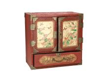 A small wooden cinebar cabinet with carved lacquer finish. Door panels with porcelain plaques, decorated with flowers and birds. Metal hinches and mounts. Inside with six drawers. Japan, 20th century. Dim. 30 x 30 x 17,5 cm.