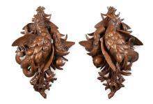 Een paar gestoken houten jachttrofeeën met voorstelling van o.a. fazanten e