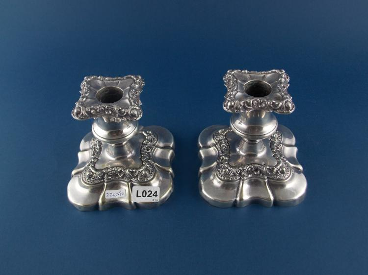 A PAIR OF SILVER-PLATED CANDLESTICKS