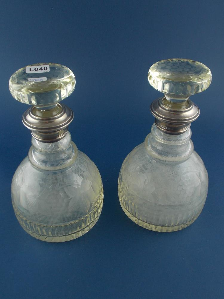 A PAIR OF CUT-CRYSTAL AND SILVER BOTTLES