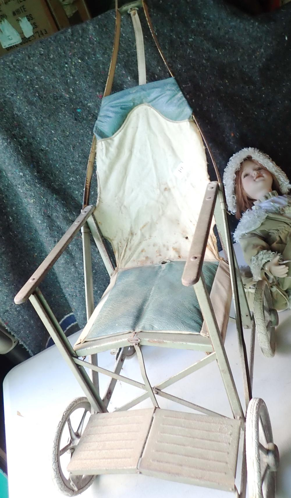 PORCELAIN DOLL IN 1950S METAL PRAM & CANVAS , NEW DOLL, KNEES PERMANENTLY BENT, PORCELAIN HEAD, LEG FROM KNEES DOWN AND ARMS, BODY ARMS & PART LEGS ARE MATERIAL