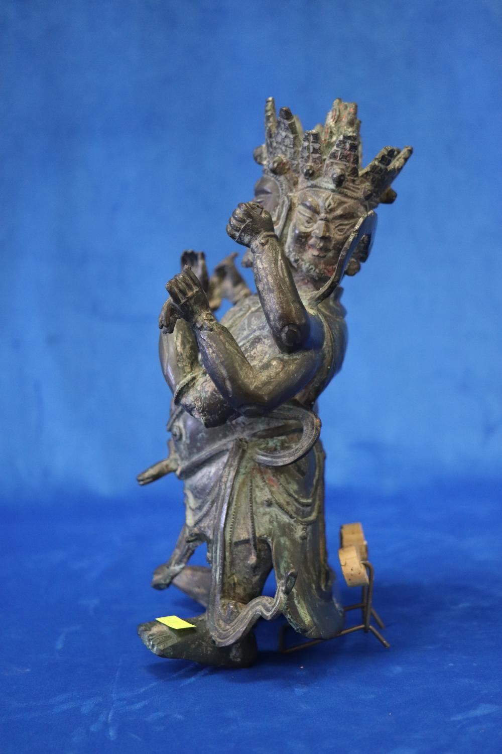 CHINESE BRONZE DEITY FIGURE, MING DYNASTY, DEITY HAS 3 FACES AND 6 ARMS EACH HOLDING AN ATTRIBUTE, 32CM H, FROM THE COLLECTION OF ROSS GORDON, SOME LOSSES,