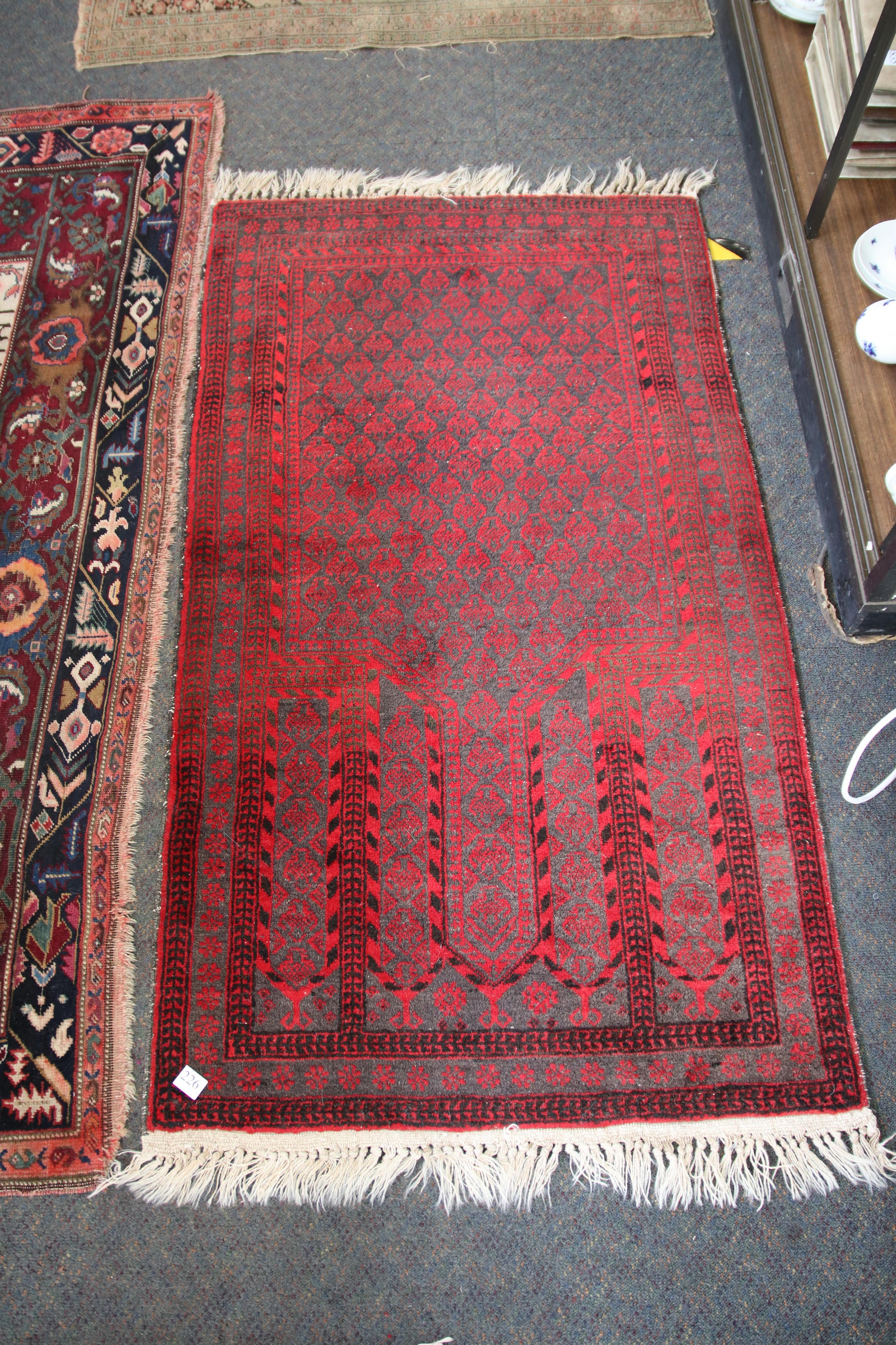 ANTIQUE PERSIAN HAND KNOTTED WOOL PRAYER RUG, RED AND BLACK MEDALLION AND BORDER PATTERN, MEASURES 146CM X 81CM (WEAR AND FRAYED EDGES)