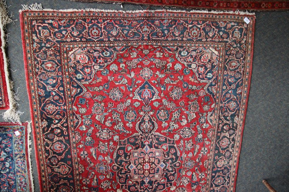 ANTIQUE PERSIAN HAND KNOTTED WOOL FLOOR RUG, RED AND BLUE MEDALLION AND BORDER PATTERN, MEASURES 138CM X 196CM (WEAR AND FRAYED EDGES)