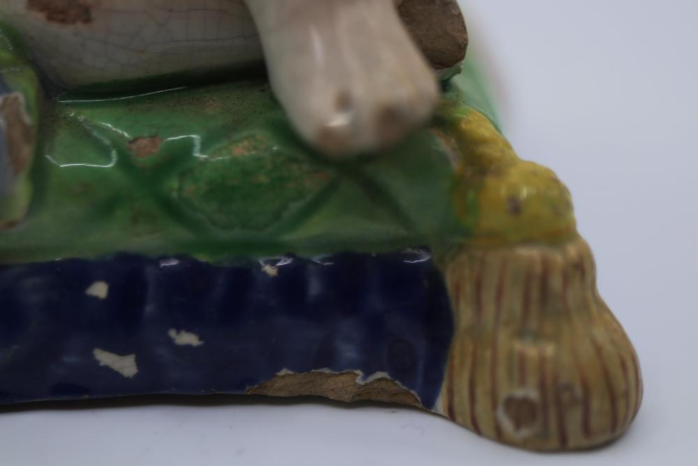 ANTIQUE DELFT WARE TIN GLAZE CANDLE HOLDER (CHIPPED & OLD FIRING CRACK) 90MM WIDE X 70MM HIGH & 18TH CENTURY POTTERY FIGURE OF A BOY (CHIPS & DAMAGE TO GLAZING) 110MM X 70MM