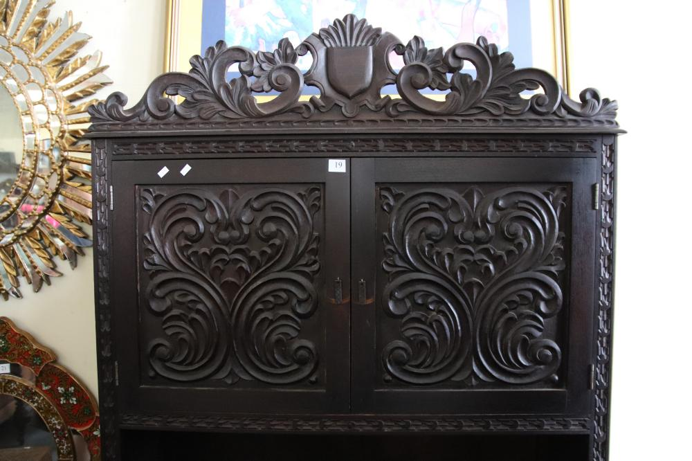 TALL PERUVIAN CARVED TIMBER CABINET WITH FOUR SCROLL CARVED DOORS AROUND AN OPEN SHELF RAISED ON FEET