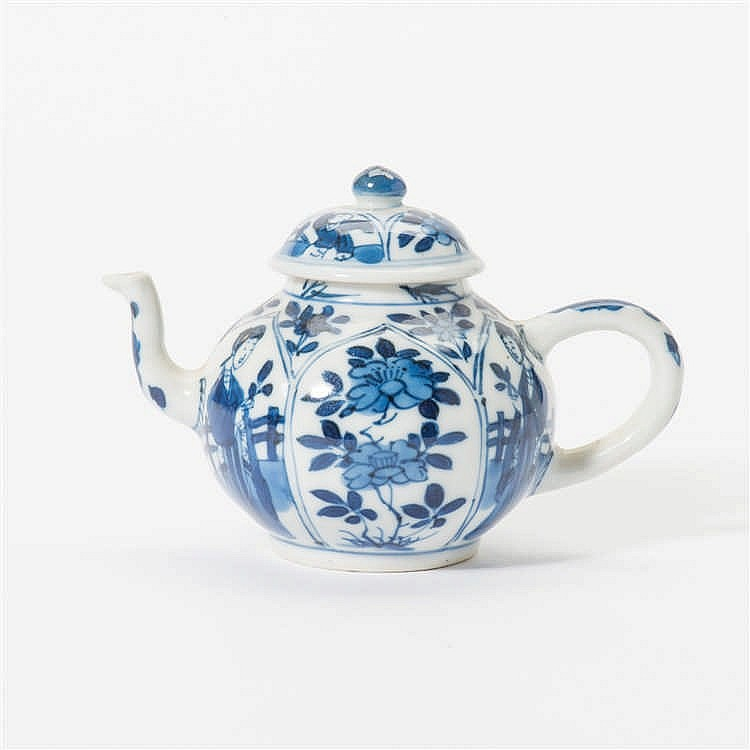 A curved blue and white teapot with lid