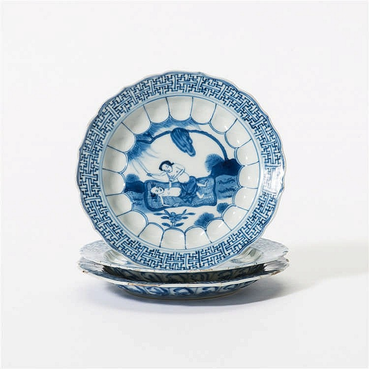 A series of three curved blue and white saucers