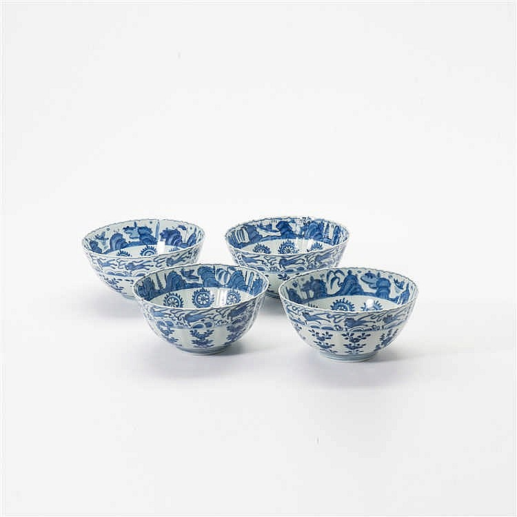 A series of four curved blue and white bowls