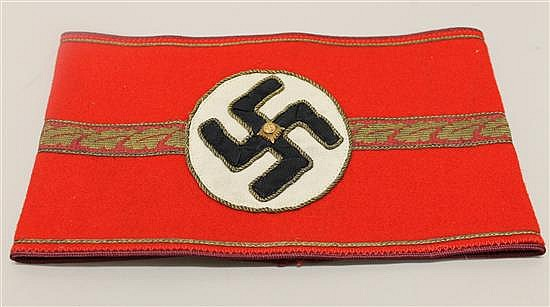 WW II German NSDAP political leader's armband. Band  is red wool with gilt bullion cord both edges, and surrounding black swastika a..