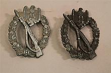 Lot of two German WW II combat badges. Lot includes two infantry assault badges, one solid back maker marked and one hollowback. Bot...