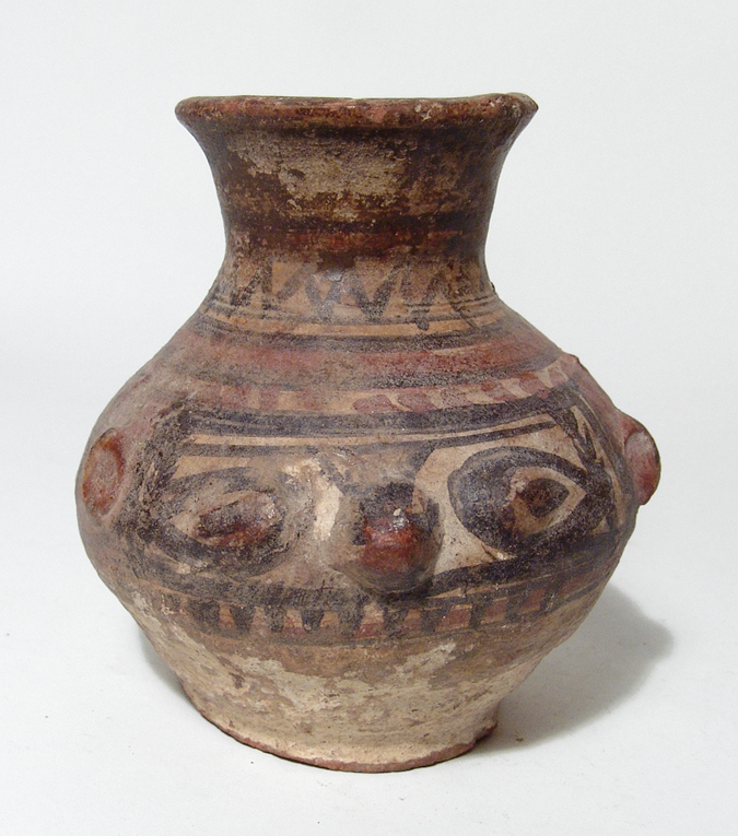 An Egyptian polychrome jar representing Bes