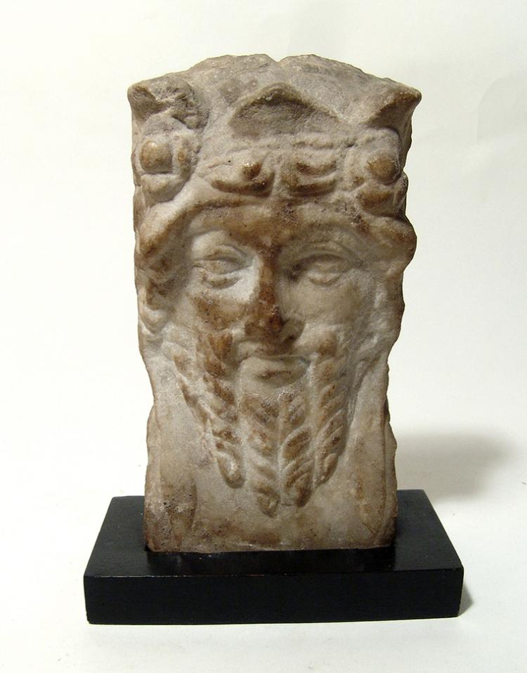 A Roman marble relief of a bearded satyr