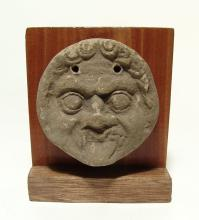 A Greek terracotta antefix depicting the face of a Gorgon