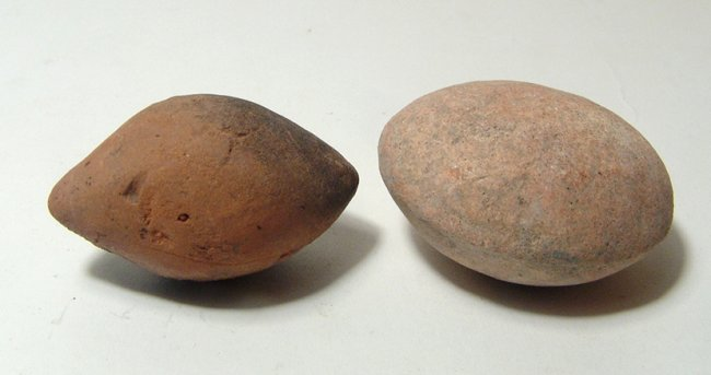 A pair of ancient clay sling bullets