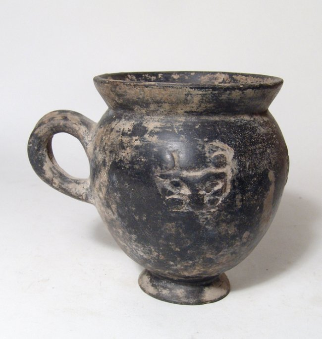 A Bucchero pesante mug with 4 lion masks