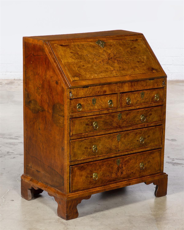 Lot - A George I/II crossbanded walnut slant front desk second quarter 18th century