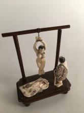 Carved Japanese figure of a nude woman suspendedwith a man standing and a robe o