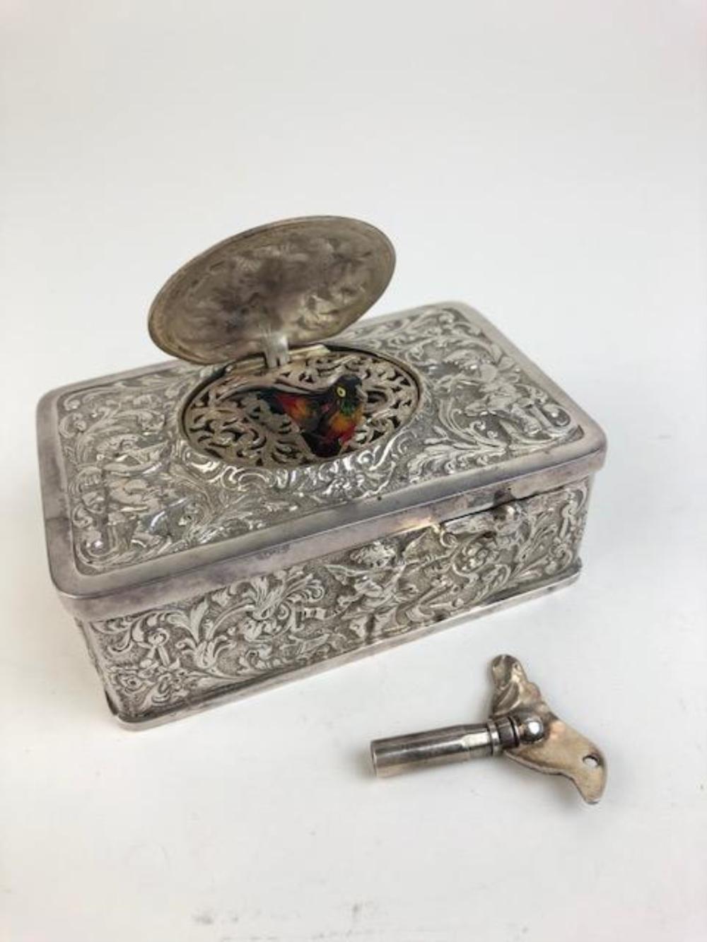 Silver mechanical singing bird box. When the slid bar is slid the lid raises an