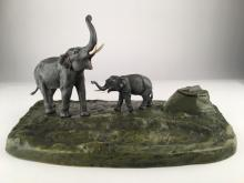 A cold painted ink well with two standing elephants withe their tusks up.