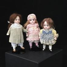 (3) GERMAN ALL BISQUE DOLLS.  ONE-PIECE HEADS AND TORSOS, STRING JOINTED ARMS AND LEGS WITH PAINTED SHOES, MOHAIR WIGS, STATIONARY G...