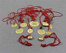 11 CHINESE YELLOW GOLD TONE CHARMS ON RED CORD, APPROX 42.3 GRAMS