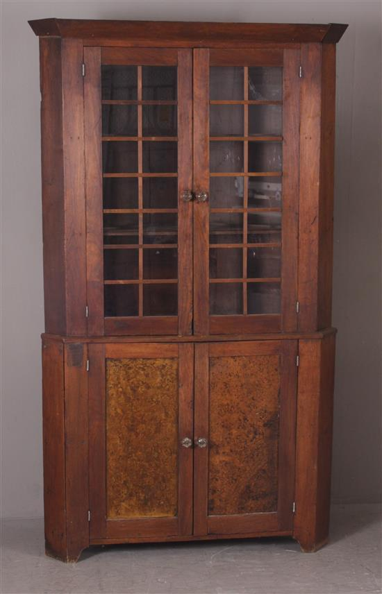 EARLY WALNUT 2 PIECE CORNER CUPBOARD WITH DECORATIVE GRAIN PAINTED BURL PANELS ON BASE, GLASS DOORS ARE SINGLE PANE (ONE IS BROKEN),...