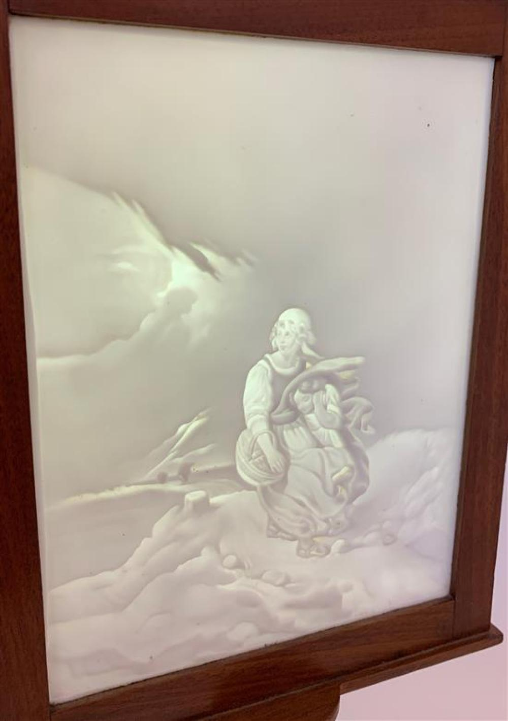 """LITHOPHANE PANEL DEPICTING MOTHER AND CHILD IN A STORM IN WOODEN FRAME, 7¼""""x 9¾"""". FRAME IS PART OF WOODEN STAND 17¾""""H"""