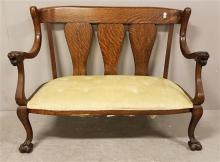 VICTORIAN OAK TRIPLE VASE BACK LOVESEAT WITH LION HEAD ARMS AND CLAW FEET AND YELLOW TUFTED UPHOLSTERY, 49