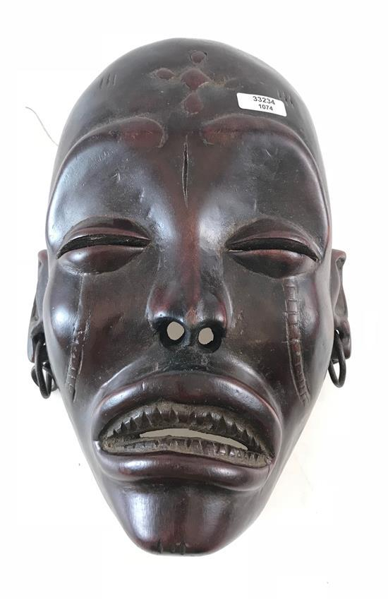 AFRICAN MASK, MADE OF POLISHED RED WOOD, FEATURING METAL EARRINGS, SQUINTED EYES, AND HOLES FOR THE ATTACHMENT OF TRADITIONAL GRASS...