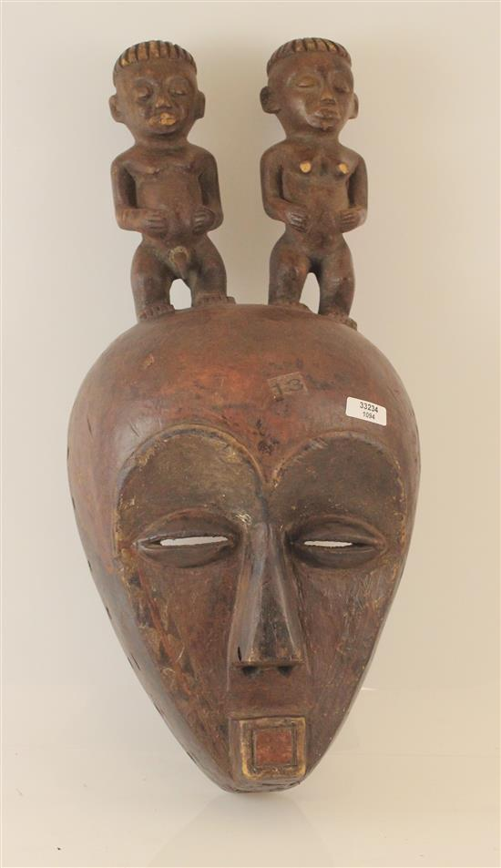 AFRICAN FERTILITY MASK FEATURING TWO SMALL FIGURES ON TOP, MADE OF WOOD.