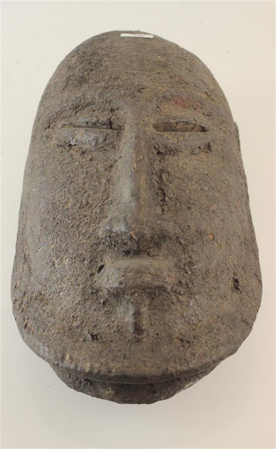 AFRICAN WOODEN MASK, ROUGH TEXTURE INDICATING IT IS USED TO WARD OF EVIL, EYES SLANTED INWARD, ELONGATED FLAT NOSE, CLOSED MOUTH AP...