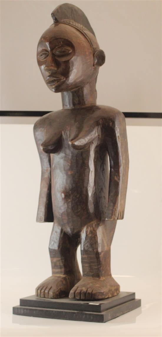 AFRICAN ART, WOODEN FIGURE OF WOMEN ARMS AND FINGERS ARE SHORT AND PLACED AT THE SIDE, SMOOTH FINISH STANDING ON CUSTOM BASE, 33.75