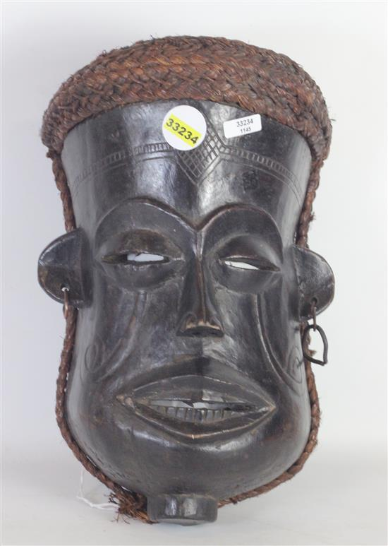 AFRICAN TRIBAL ART, HAND CARVED WOODEN MASK, EYES ARE SQUINTED, MOUTH IS OPEN, EARS ARE PIERCED WITH METAL EARRINGS, STRAW LIKE BRAI...