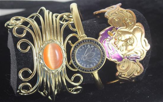 THREE GOLD TONE METAL CUFFS INCLUDING: OPENWORK WITH ORANGE STONE CABACHON, HINGED WITH INSET ITALIAN CURRENCY WITH PAVE HALO, AND A...