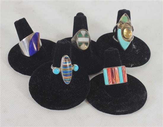 LOT OF FIVE SOUTHWESTERN STYLE RINGS INCLUDING: SIZE 5 WITH DUAL TONE GEOMETRIC OVAL, SIZE 6 FREEFORM SHANK WITH BLUE ENAMEL, ANGLED...