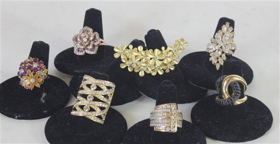 SEVEN GOLD TONE RINGS INCLUDING: SIZE 6 DOUBLE SHANK WITH INSET CZ STONES IN FLORAL MOTIF, DOUBLE LOOPED FREEFORM SHANK WITH PAVE SE...