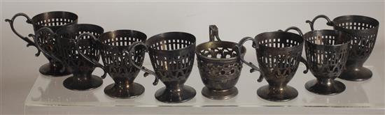 EIGHT OPENWORK SILVER TONE EGG CUPS WITH HANDLES INCLUDING: SEVEN UNMARKED HEAVILY TARNISHED, AND ONE MARKED STERLING. STERLING 0.82...