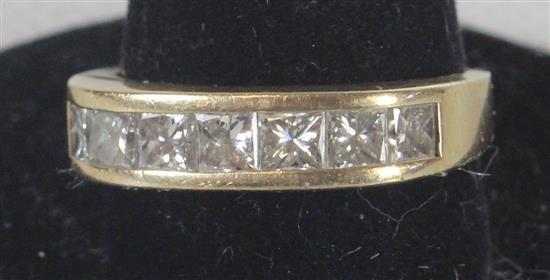 MARKED 14KT YELLOW GOLD RING. SIZE 5.75 TAPERED SHANK WITH SEVEN PRINCESS CUT CHANNEL SET DIAMONDS. 3.8 GRAMS TW.